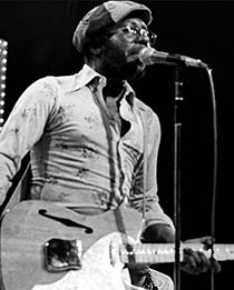 Curtis Mayfield playing guitar and singing