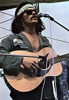 Country Joe McDonald playing at woodstock 1969
